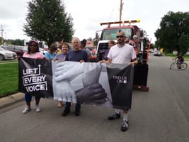 Lift Every Voice marching in a local parade with banner.